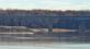 A motor boat cruises down the river by the Illinois bridge.. Taken March 16, 2020 Riverwalk, Dubuque, IA by Veronica McAvoy.