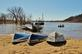 Three overturned boats line the shore of a lake while a fishing boat goes out on the river.. Taken March 18, 2021 O'Leary's Lake, WI by Veronica McAvoy.