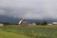 Dark storm clouds frame the backgroud to a red barn.. Taken August 16, 2018 Near Lamotte, Iowa by Veronica McAvoy.