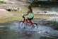 A girl rides her bike through the creek.. Taken July 27, 2018 Swiss Valley camp grounds, Dubuque, IA by Veronica McAvoy.